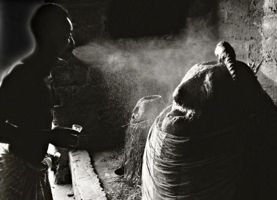 Togo_Seko_1989Assistant-d'un-prêtre-vaporisant-de-l'alcool-de-palme-sur-le-vodu-Djagli-min